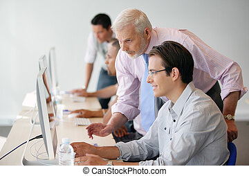 Manager in discussion with a younger worker using a computer
