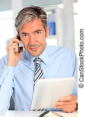 Manager in office talking on mobile phone
