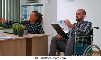 Handicapped company manager in wheelchair giving advice about financial project to partner in office room company room analysing graphs from documents. Discussing and pointing on computer desktop