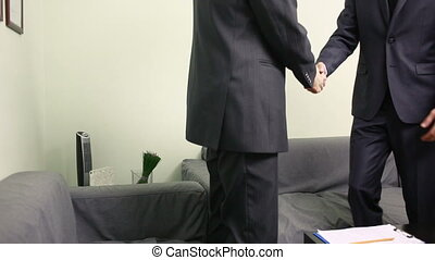 Manager interviewing a male applicant in his office. Two men in business suits
