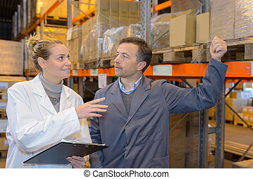 manager is showing shelves to the worker in a warehouse