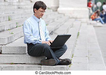 Young manager working with his laptop in city environment, sitting on flight of strairs