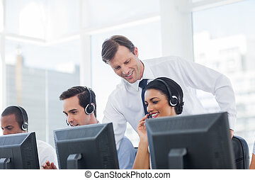Manager listening to call centre employee working on...