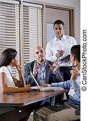 Manager meeting with office workers, directing - Hispanic...