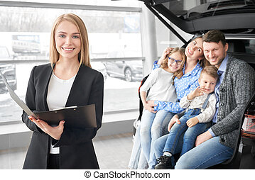 Manager of car dealership and happy family posing, smiling.