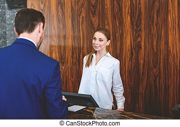 Manager of hotel registering new guest