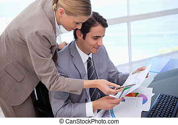 Manager pointing at something to her employee on a graph