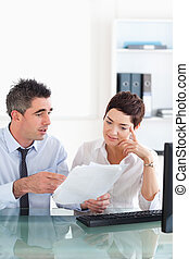Manager pointing at something to his secretary on a blueprint document in an office