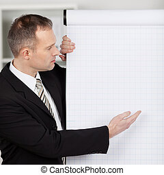Manager pointing to flipchart - Manager in office pointing...