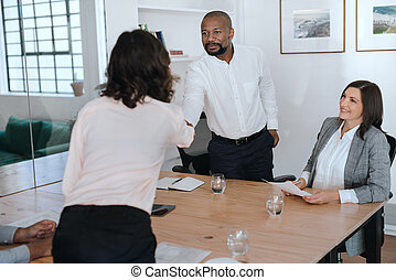 Manager shaking hands with an employee during a meeting