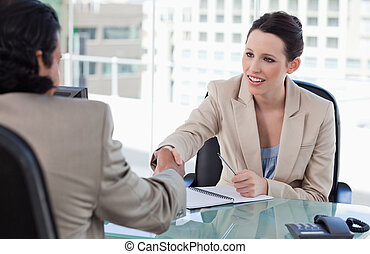 Manager shaking the hand of a male applicant in her office