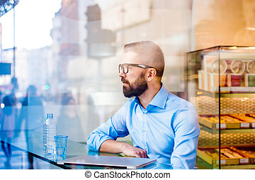Manager sitting in cafe by the window, drinking water