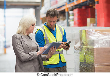 Manager using tablet while worker scanning package in...