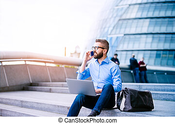 Manager with laptop and smart phone, London City Hall