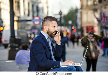 Manager with laptop and smart phone, sunny Piccadilly Circus