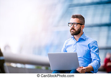 Manager with laptop, sitting on stairs, London, City Hall - ...