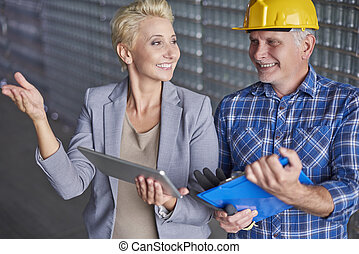 Manager with manual worker in warehouse