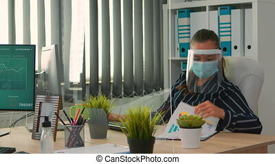 Businesswoman with visor and protection mask working in new normal business office. Freelancer discussing with colleague in financial company respecting social distance during global pandemic.