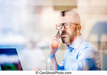Manager working on laptop by window, making phone call