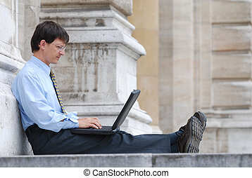 Young manager working with his laptop in city environment
