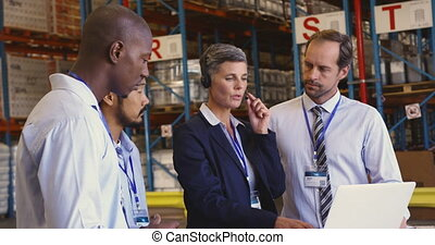Managers and staff having a meeting in a warehouse loading ...