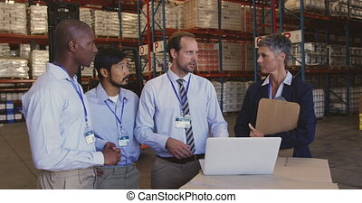 Managers and staff talking in a warehouse laoding bay 4k - ...