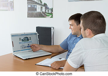 Managers Discussing Business Using Laptop