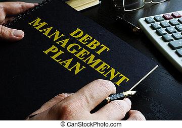 Managing Debt concept.   Book with title Debt Management Plan (DMP).