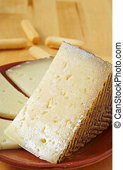 manchego cheese from Spain - closeup of a piece and some...
