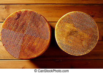 Manchego cheese from Spain in wooden table two whole pieces
