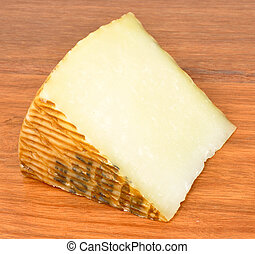 Manchego Cheese - Wedge of traditional Manchego cheese on a...