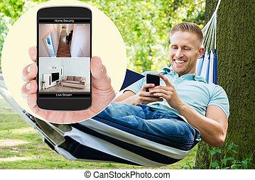 mand, kigge hos, security til hjem, system, på, mobilephone