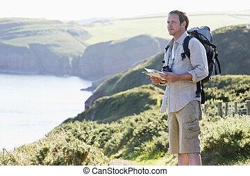 mand stå, på, cliffside, sti, holde, kort