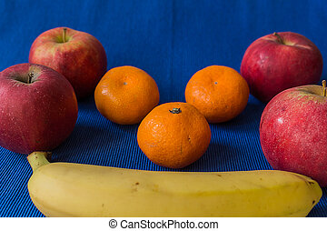 Mandarin Apples and Bananas on blue background