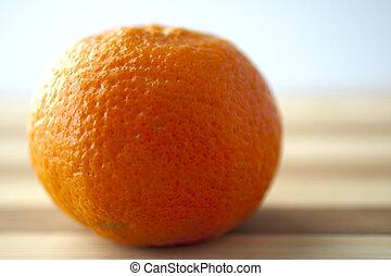 Mandarin - Closeup of an entire mandarin over a wooden...