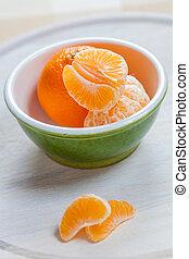 Mandarin orange segments in a green bowl