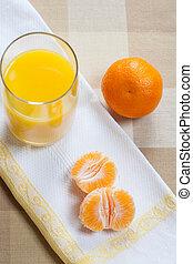 Mandarin orange segments with a glass of orange juice