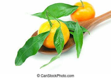 mandarin with green leaves on a wooden spoon isolated on...