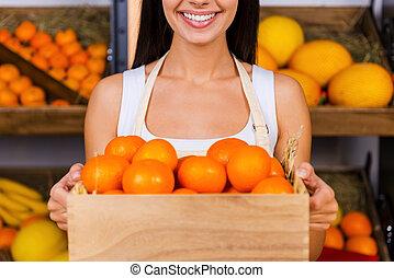 mandarinok, helyett, you., körbevágott, kép, közül, gyönyörű, kisasszony, alatt, kötény, birtok, fából való, konténer, noha, mandarinok, és, mosolygós, időz, álló, alatt, élelmiszerbolt, noha, változatosság gyümölcs, alatt, a, háttér