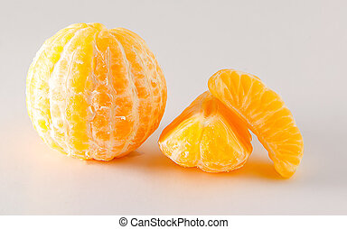 mandarins stripped whole and in slices on white background
