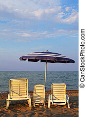 MANDATORICCIO, ITALY – JULE 20: Three lounge chairs for family on beach. Mother, father, child on Jule 20, 2010 in Mandatoriccio, Calabria, Italy. Calabria region visited annually by only 3% of Ital