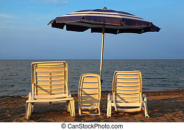 MANDATORICCIO, ITALY – JULE 20: Three lounge chairs on beach...