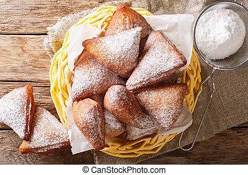 Mandazi is a slightly sweet East African Street Food; spicy, airy yeast doughnut dough made with coconut milk, flavored with cardamom. Horizontal top view