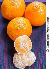 Manderin orange segments with three whole manderins