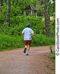 mandlig, person løbe, på, grus vej, ind, den, skov