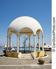 Mandraki harbour embankment pavilion with decorative iron tree and bird inside. Rhodes, Greece.