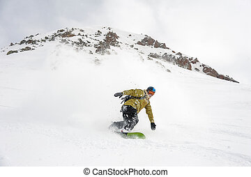 Manful snowboarder moving down the hill in the mountain ...