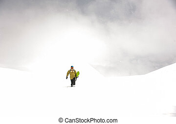 Manful snowboarder walking down the hill in the mountain ...