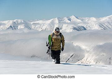 Manful snowboarder walking in the mountain resort - Manful ...