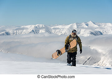 Manful snowboarder walking with the brown snowboard in the ...